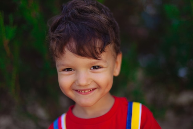 A happy child looks into the camera bright and colorful portrait of a brave boy in a red tshirt on a...