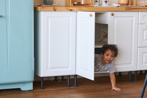 A happy child looks out of the closet in the kitchen