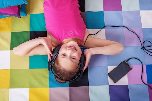 Happy child lying and listening to music.  childhood and music.