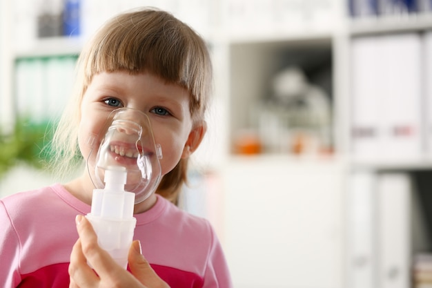 Happy child makes inhalation at home for