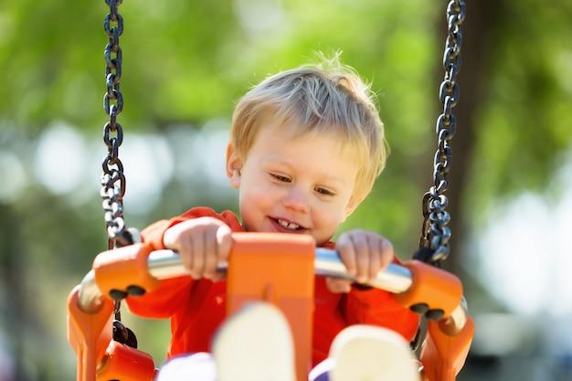 Счастливый ребенок на оранжевом качели