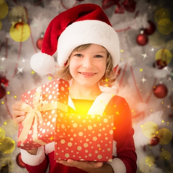 幸せな子供が魔法のクリスマスギフトボックスを開きます。クリスマスの休日の概念