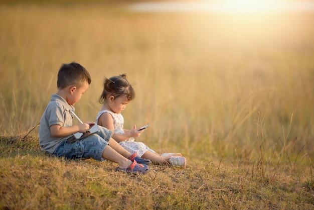 幸せな子全体的にタブレットと携帯電話を日当たりの良いフィールド、夏のアウトドアライフスタイル、居心地の良い気分で遊んで