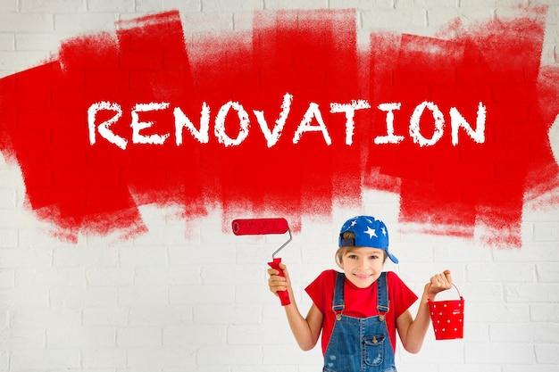 Счастливый ребенок, рисующий на стене. малыш играет дома. весенний ремонт и концепция дизайна
