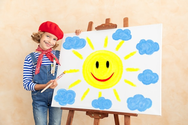 キャンバスに太陽と雲を描いて幸せな子。