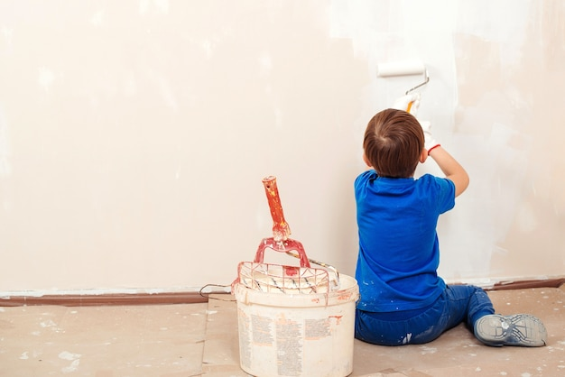Happy child paints the wall. repair in the apartment. cute boy with a paint roller. new house for family.