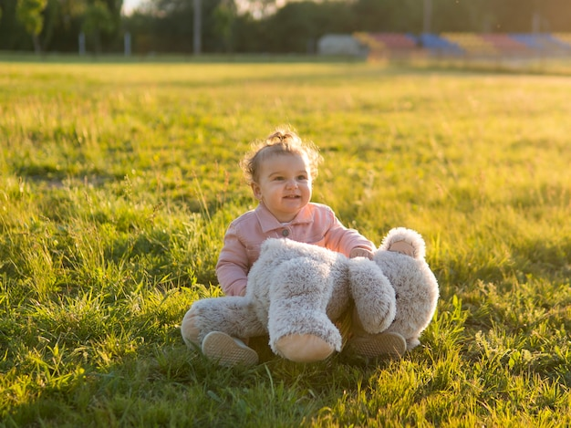 Happy child in pink clothes and teddy bear