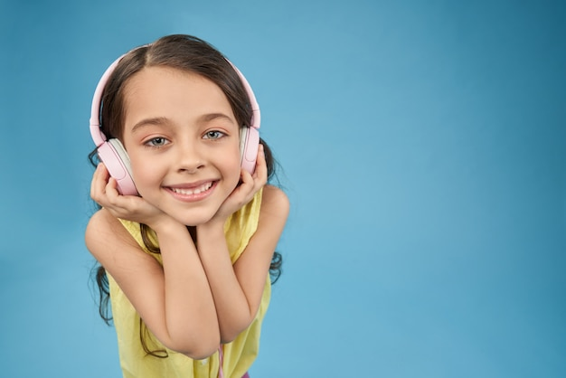 Happy child in pink headphones smiling, looking at camera.