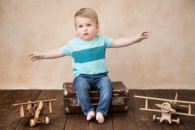 집에서 놀고 행복 한 아이입니다. 장난감 비행기와 아기