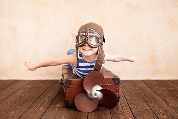 家で遊んで幸せな子。夏休みと旅行を夢見ている笑顔の子供。想像力と自由の概念