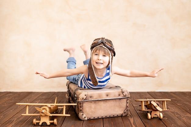 家で遊んで幸せな子。夏休みと旅行を夢見ている笑顔の子供。