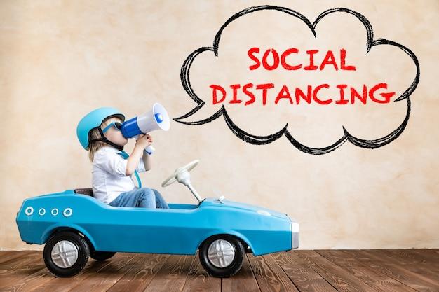 家で遊んで幸せな子。コロナウイルス感染の懸念の可能性による社会的距離