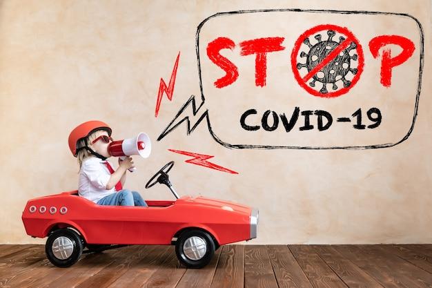 家で遊んで幸せな子。世界的なパンデミックコロナウイルスcovid-19の概念を停止します