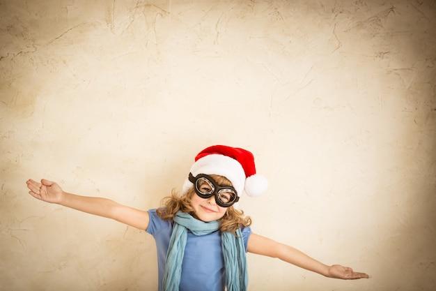 그런 지 벽 배경에 조종사 옷을 입고 노는 행복 한 아이. 레트로 톤