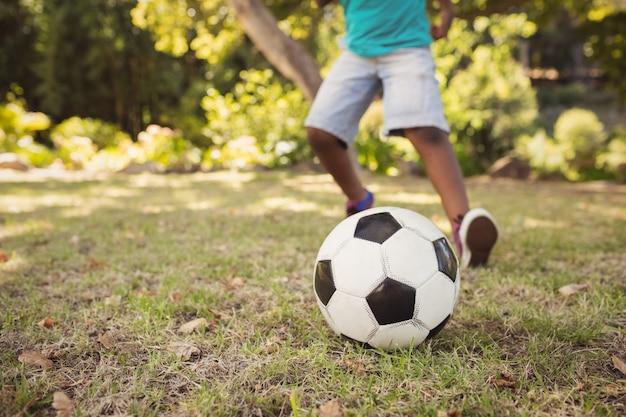Счастливый ребенок играет в футбол