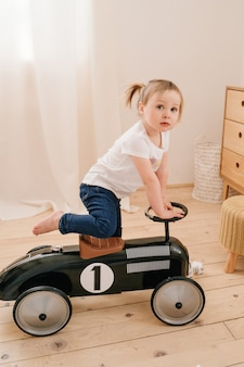 Happy child playing at home. a girl with ponytails plays in the room and rides a retro toy car.
