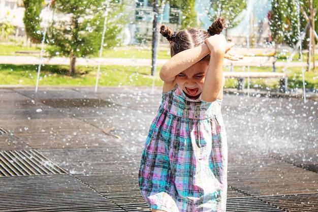 噴水選択フォーカスで遊んで幸せな子。人々
