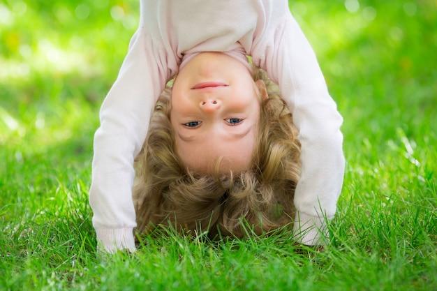 Счастливый ребенок играет на зеленой траве в весеннем парке