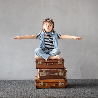 屋外で遊んで幸せな子。夏休みと旅行を夢見ている笑顔の子供。想像力と自由の概念