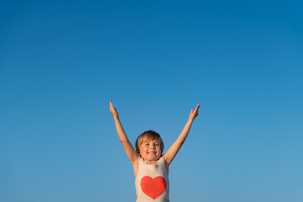 青い春の空の壁に対して屋外で遊ぶ幸せな子