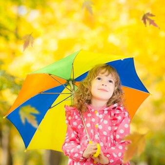 秋の公園で屋外で遊ぶ幸せな子