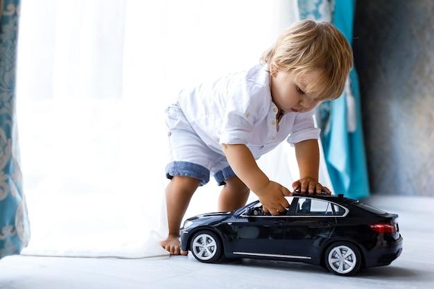 집에서 큰 검은 장난감 자동차를 가지고 노는 행복한 아이 아이에 초점