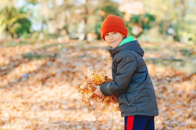 Счастливый ребенок, играя с осенними листьями в парке. осеннее настроение.