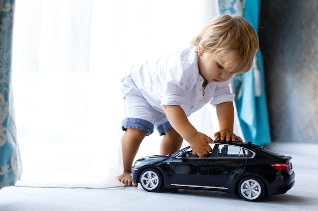 Happy child playing with a big black toy car at home focus on the child