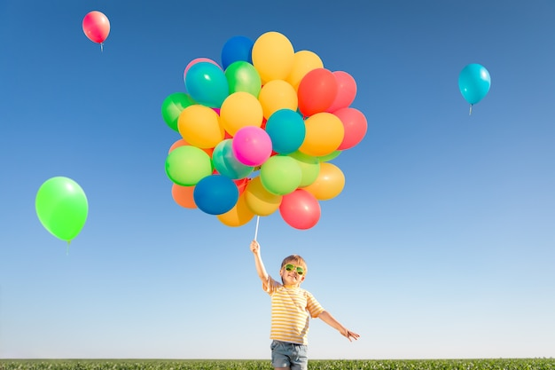 屋外で明るい色とりどりの風船で遊んで幸せな子。青い空を背景に緑の春の野原で楽しんでいる子供。健康的でアクティブなライフスタイルのコンセプト