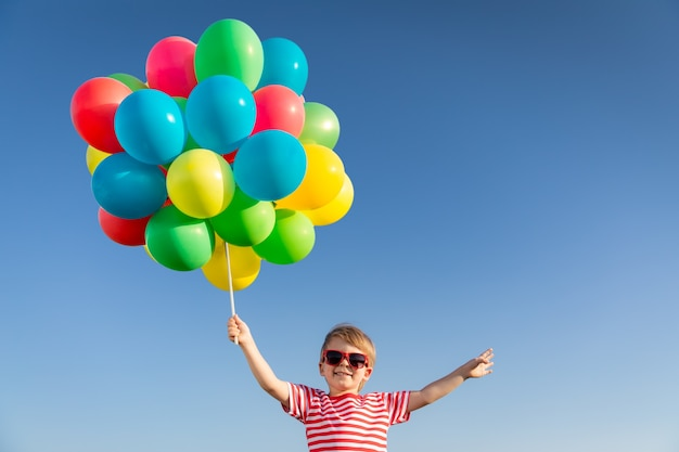 屋外で明るい色とりどりの風船で遊ぶ幸せな子供 Premium写真