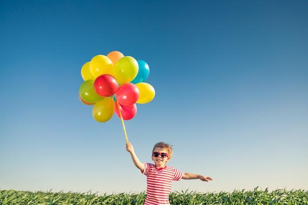 屋外で明るい色とりどりの風船で遊んで幸せな子。
