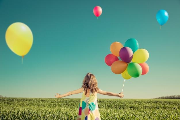 屋外でカラフルなおもちゃの風船で遊んで幸せな子。青い空を背景に緑の春のフィールドで楽しんで笑っている子供。自由の概念