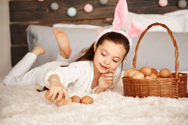Happy child playing with eggs in bedroom