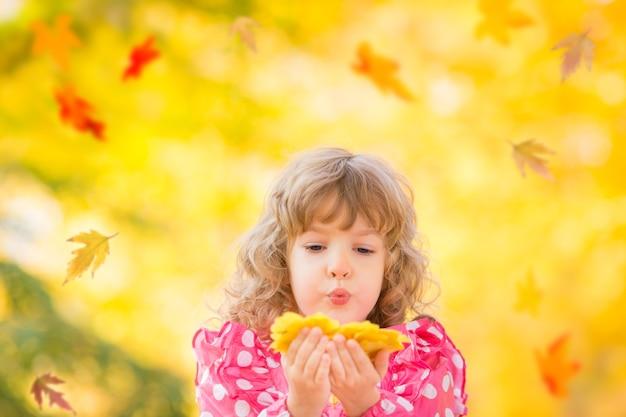 秋の公園で屋外の葉で遊ぶ幸せな子