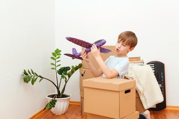 Счастливый ребенок, играя с самолетом в новом доме. жилье молодой семьи с детьми. милый ребенок помогает распаковывать коробки. семья переезжает в новую квартиру.
