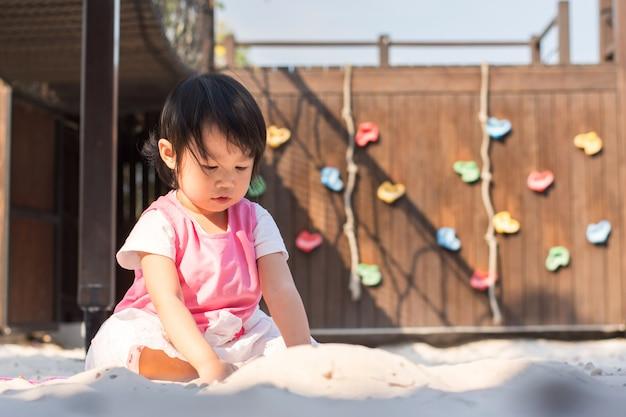 遊び場で砂で遊んで幸せな子供