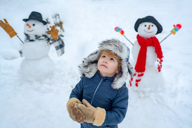 Happy child playing with snowball against white winter background winter portrait of cute child in s...