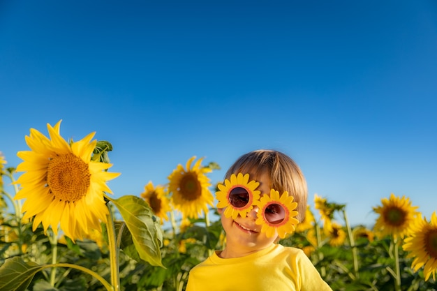 Happy child playing with sunflower outdoor. kid having fun in green spring field against blue sky background.