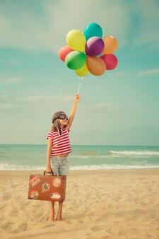 바다와 하늘에 대 한 장난감 공기 풍선을 가지고 노는 행복 한 아이 아이 파일럿 재미 야외 여름 휴가 및 여행 개념 자유와 상상력