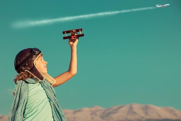 산에 대 한 장난감 비행기와 하늘 배경에서 비행기를 가지고 노는 행복 한 아이