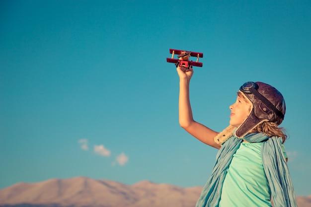산과 하늘 배경에 장난감 비행기를 가지고 노는 행복한 아이