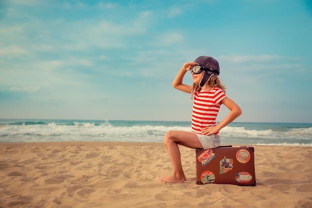 바다와 하늘에 대 한 장난감 비행기를 가지고 노는 행복 한 아이 아이 파일럿 재미 야외 여름 휴가 및 여행 개념 자유와 상상력