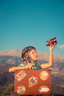 장난감 비행기와 산과 하늘 배경에 빈티지 가방을 가지고 노는 행복한 아이