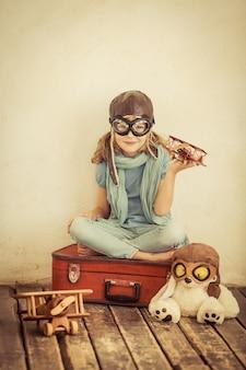 집에서 장난감 비행기를 가지고 노는 행복한 아이. 레트로 톤