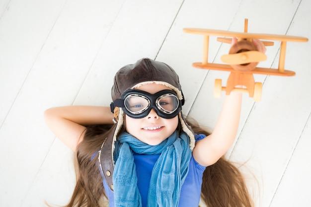 장난감 비행기를 가지고 노는 행복한 아이. 집에서 나무 바닥에 누워 있는 아이