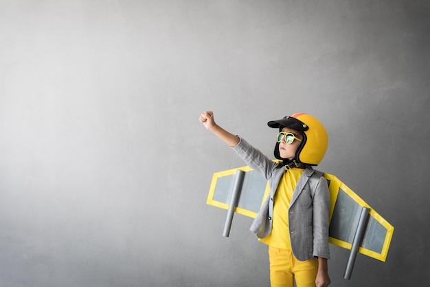 Счастливый ребенок играет с игрушечным реактивным ранцем