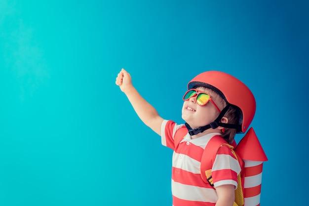 파란색 벽에 장난감 종이 로켓을 가지고 노는 행복 한 아이.