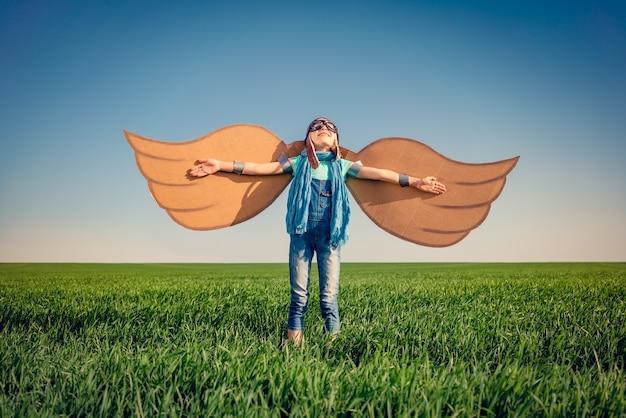 녹색 스프링 필드에서 장난감 종이 날개를 가지고 노는 행복 한 아이