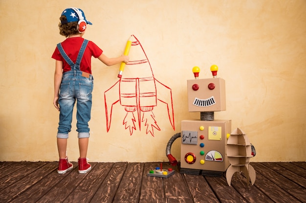 집에서 장난감 로봇을 가지고 노는 행복한 아이. 혁신 기술 및 성공 개념