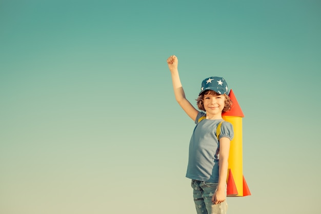 여름 하늘 배경에 장난감 로켓을 가지고 노는 행복한 아이. 레트로 톤